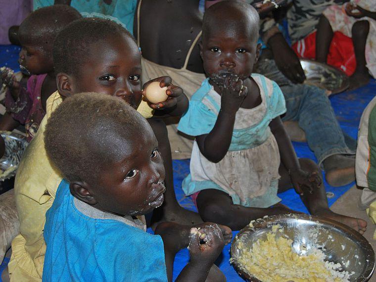 Afrikanische Kinder essen zu dritt aus einer Schüssel.